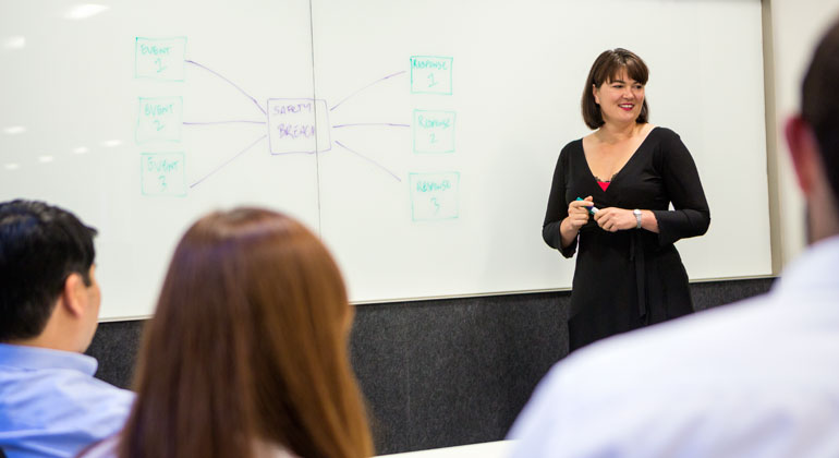 Woman discussing diagrams on whiteboard in meeting